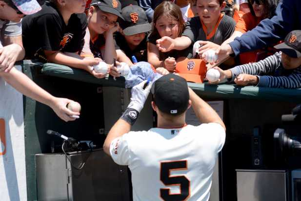 San Francisco Giants catcher Nick Hundley (5) signs autographs for fans as the Miami Marlins face the San Francisco Giants at AT&T Park on Friday, July 9, 2017.