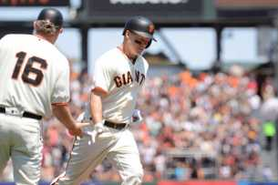 San Francisco Giants catcher Nick Hundley (5) high-fives Giants third base coach Phil Nevin (16) after hitting a solo home run in the fifth inning as the Miami Marlins face the San Francisco Giants at AT&T Park on Friday, July 9, 2017.