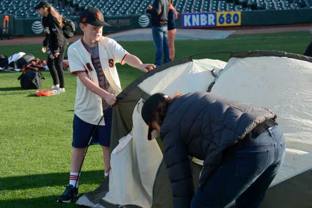 Archie Paul (left), 11, and his mother Laurel Paul (right), 46, an attorney from San Francisco, Calif., pitch a tent on the field at the Giants slumber party after the Miami Marlins beat the San Francisco Giants at AT&T Park on Friday, July 9, 2017.