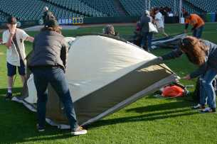 Archie Paul (left), 11, and his mother Laurel Paul (center), 46, an attorney from San Francisco, Calif., pitch a tent on the field at the Giants slumber party after the Miami Marlins beat the San Francisco Giants at AT&T Park on Friday, July 9, 2017.