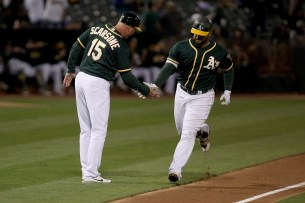 Oakland Athletics third base coach Steve Scarsone (15) congratulates Oakland Athletics first baseman Yonder Alonso (17) after a home run as the Cleveland Indians face the Oakland Athletics at Oakland Coliseum in Oakland, Calif., on Friday, July 14, 2017.