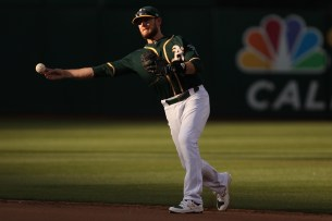 Oakland Athletics second baseman Jed Lowrie (8) fields a ground ball to end the fourth inning as the Cleveland Indians face the Oakland Athletics at Oakland Coliseum in Oakland, Calif., on Saturday, July 15, 2017.