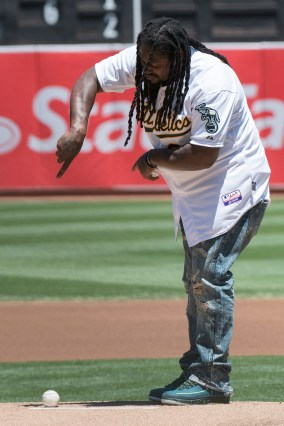 Oakland Raiders running back Marshawn Lynch (24) goofs around on the mound before throwing out the ceremonial first pitch prior to the game between Cleveland Indians and the Oakland Athletics at the Oakland Coliseum in Oakland, Calif., on July 16, 2017.