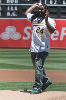 Oakland Raiders running back Marshawn Lynch (24) throws out the ceremonial first pitch prior to the game between Cleveland Indians and the Oakland Athletics at the Oakland Coliseum in Oakland, Calif., on July 16, 2017.
