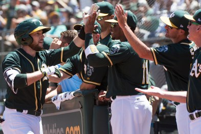 Oakland Athletics second baseman Jed Lowrie (8) is congratulated at the dugout after hitting a home run in the third inning of the game against the Cleveland Indians at the Oakland Coliseum in Oakland, Calif., on July 16, 2017.
