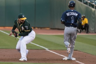 Oakland Athletics first baseman Yonder Alonso (17) looks back at a misplayed ball as Tampa Bay Rays second baseman Tim Beckham (1) safely reaches first in the second inning of the game against the Tampa Bay Rays at the Oakland Coliseum in Oakland, Calif., on July 17, 2017.