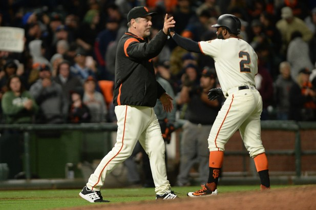 San Francisco Giants manager Bruce Bochy (15) high fives center fielder Denard Span (2) after the San Francisco Giants walk off with a 2-1 victory over the Cleveland Indians at AT&T Park in San Francisco, Calif., on Tuesday, July 18, 2017.
