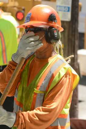 A San Francisco Public Works crew member covers his face to avoid inhaling dust at a tree maintenance program launch in Noe Valley in San Francisco, Calif. on Wednesday, July 19, 2017.