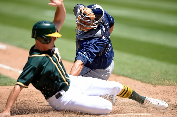 Tampa Bay Rays catcher Wilson Ramos (40) applies a late tag on Oakland Athletics center fielder Jaycob Brugman (38) in the fifth inning as the Tampa Bay Rays face the Oakland Athletics at Oakland Coliseum in Oakland, Calif., on Wednesday, July 19, 2017.