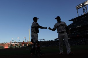 San Francisco Giants catcher Buster Posey (28) and San Francisco Giants relief pitcher George Kontos (70) bump fists before the game as the San Diego Padres face the San Francisco Giants at AT&T Park in San Francisco, Calif., on Thursday, July 20, 2017.
