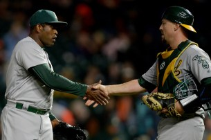 Oakland Athletics relief pitcher Santiago Casilla (46) and Oakland Athletics catcher Ryan Lavarnway (30) celebrate a 6-1 victory against the San Francisco Giants at AT&T Park in San Francisco, Calif., on Tuesday, August 2, 2017.