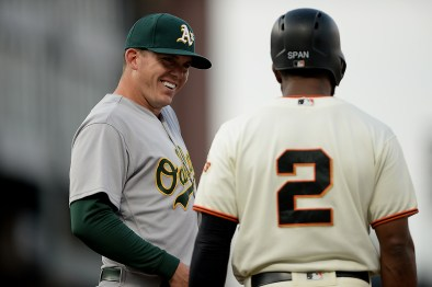 Oakland Athletics designated hitter Ryon Healy (25) chats with San Francisco Giants center fielder Denard Span (2) during an official review in the first inning as the Oakland Athletics face the San Francisco Giants at AT&T Park in San Francisco, Calif., on Thursday, August 3, 2017.