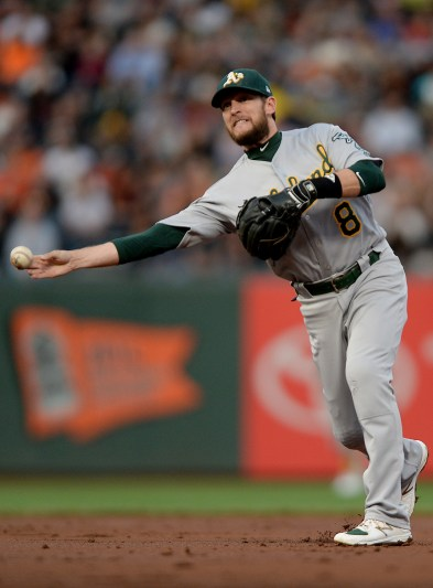 Oakland Athletics second baseman Jed Lowrie (8) throws out San Francisco Giants right fielder Hunter Pence (8) in the first inning as the Oakland Athletics face the San Francisco Giants at AT&T Park in San Francisco, Calif., on Thursday, August 3, 2017.