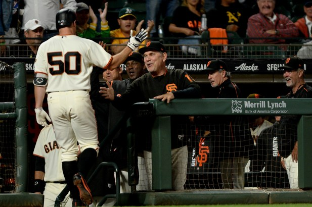 San Francisco Giants relief pitcher Ty Blach (50) is congratulated by San Francisco Giants manager Bruce Bochy (15) after a home run in the fifth inning as the Oakland Athletics face the San Francisco Giants at AT&T Park in San Francisco, Calif., on Thursday, August 3, 2017.