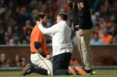 San Francisco Giants first baseman Brandon Belt (9) is checked out by trainer Dave Groeschner after being hit by a pitch in the sixth inning as the Arizona Diamondbacks face the San Francisco Giants at AT&T Park in San Francisco, Calif., on Friday, August 4, 2017.