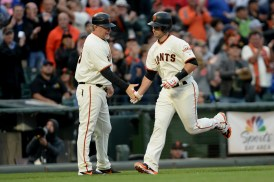 San Francisco Giants catcher Buster Posey (28) is congratulated by San Francisco Giants third base coach Phil Nevin (16) after a 3-run home run in the first inning as the Chicago Cubs face the San Francisco Giants at AT&T Park in San Francisco, Calif., on Tuesday, August 8, 2017.