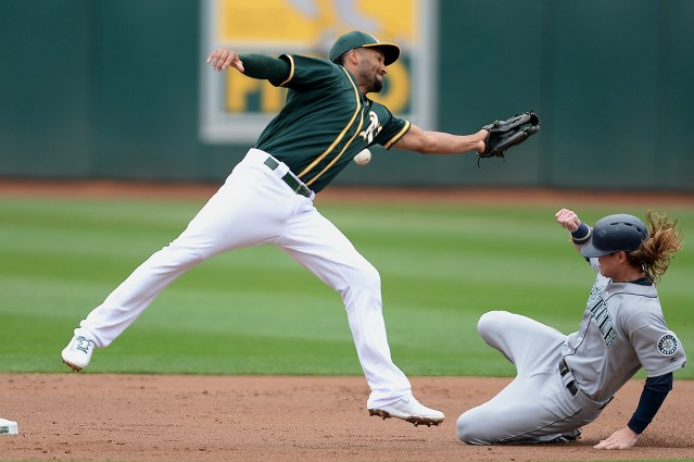 Seattle Mariners left fielder Ben Gamel (16) slides safely into second base after Oakland Athletics shortstop Marcus Semien (10) can't grab an errant throw as the Seattle Mariners face the Oakland Athletics at Oakland Coliseum in Oakland, Calif., on Wednesday, August 9, 2017.