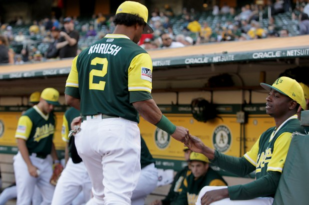 "Oakland Athletics left fielder Khris ""Khrush"" Davis (2) snap fingers with Oakland Athletics starting pitcher Jharel Cotton (45) as the Texas Rangers face the Oakland Athletics at Oakland Coliseum in Oakland, Calif., on Friday, August 25, 2017."