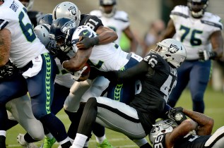 Seattle Seahawks running back Chris Carson (32) is brought down by Oakland Raiders linebacker LaTroy Lewis (46) in the first quarter as the Seattle Seahawks face the Oakland Raiders at Oakland Coliseum in Oakland, Calif., on Thursday, August 31, 2017.