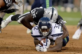 Seattle Seahawks running back Chris Carson (32) is tackled by Oakland Raiders linebacker Nicholas Morrow (35) as the Seattle Seahawks face the Oakland Raiders at Oakland Coliseum in Oakland, Calif., on Thursday, August 31, 2017.