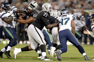 Oakland Raiders offensive guard Jordan Simmons (65) loses his helmet as quarterback EJ Manuel (3) runs for extra yardage in the first half as the Seattle Seahawks face the Oakland Raiders at Oakland Coliseum in Oakland, Calif., on Thursday, August 31, 2017.