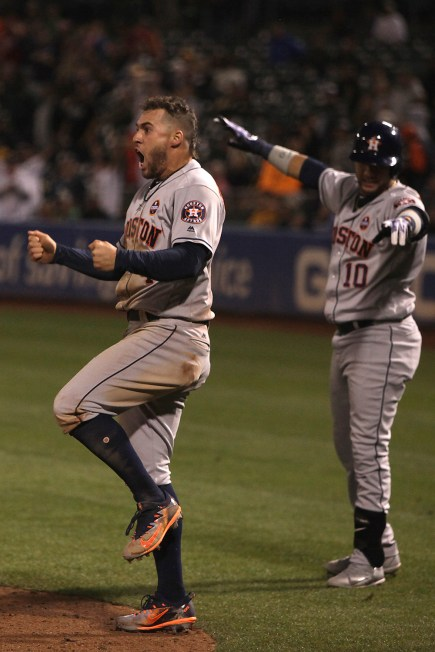 Houston Astros right fielder George Springer (4) celebrates a score in the ninth inning as the Houston Astros face the Oakland Athletics at Oakland Coliseum in Oakland, Calif., on Friday, September 8, 2017.
