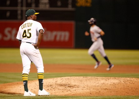 Oakland Athletics starting pitcher Jharel Cotton (45) stands on the mound as Houston Astros left fielder Josh Reddick (22) rounds the bases after a two run home run during the fifth inning of their game against the Houston Astros at the Oakland Coliseum on Friday September 08, 2017. Athletics won 9-8.