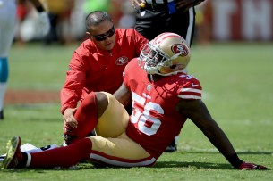 San Francisco 49ers' Reuben Foster (56) is looked at as he goes down in the first half as the Carolina Panthers face the San Francisco 49ers at Levi's Stadium in Santa Clara, Calif., on Sunday, September 10, 2017.