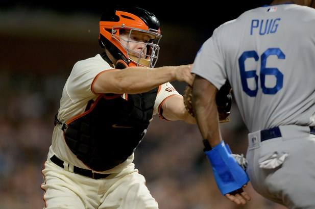 San Francisco Giants catcher Nick Hundley (5) tags out Los Angeles Dodgers right fielder Yasiel Puig (66) in the fourth inning as the Los Angeles Dodgers face the San Francisco Giants at AT&T Park in San Francisco, Calif., on Wednesday, September 13, 2017.