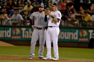 Oakland Athletics designated hitter Ryon Healy (25) and Seattle Mariners first baseman Yonder Alonso (10) chat on base in the second inning as the Seattle Mariners face the Oakland Athletics at Oakland Coliseum in Oakland, Calif., on Monday, September 25, 2017.