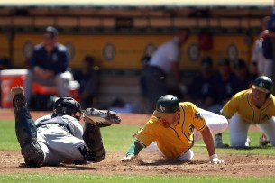 Oakland Athletics right fielder Matt Joyce (23) slides into home base as Seattle Mariners catcher Mike Marjama (28) tries to tag him out in the first inning as the Seattle Mariners take on the Oakland Athletics at the Oakland Coliseum on Wednesday, September 27, 2017.