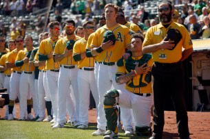 Oakland Athletics catcher Bruce Maxwell (13)takes a knee during the national anthem before the game against the Seattle Mariners at the Oakland Coliseum on Wednesday, September 27, 2017.