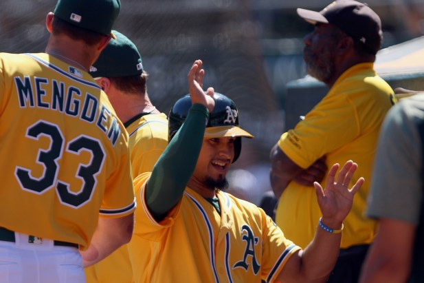 Oakland Athletics infielder Franklin Barreto (1) gives high fives after scoring a point in the third inning as the Seattle Mariners take on the Oakland Athletics at the Oakland Coliseum on Wednesday, September 27, 2017.