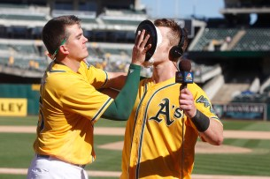 Oakland Athletics left fielder Mark Canha (20) gets a pie to the face by Oakland Athletics designated hitter Ryon Healy (25) after their game against the Seattle Mariners at the Oakland Coliseum on Wednesday, September 27, 2017. Athletics won 6-5