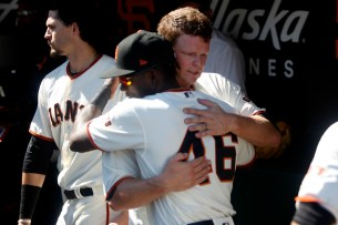 San Francisco Giants pitcher Matt Cain (18) hugs San Francisco Giants Orlando Calixte(46) in the dugout after pitching his last inning as the San Diego Padres take on the San Francisco Giants at AT&T Park on Saturday, September 30, 2017.