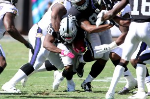 Oakland Raiders running back Jalen Richard (30) gets tackled after attempting to run the ball in the first quarter as the Baltimore Ravens take on the Oakland Raiders at the Oakland Coliseum on Sunday, October 8, 2017. The Ravens won 30-17.