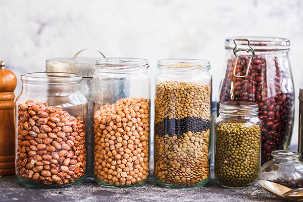 Lentils, peas, soybeans and red beans in glass jars.