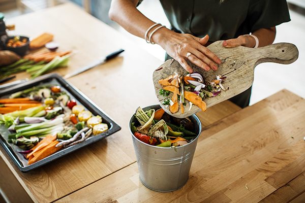 Woman putting vegetable scraps in compost pail