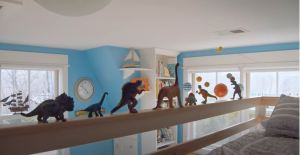 dinosaurs lined up on the ledge of a bunk bed
