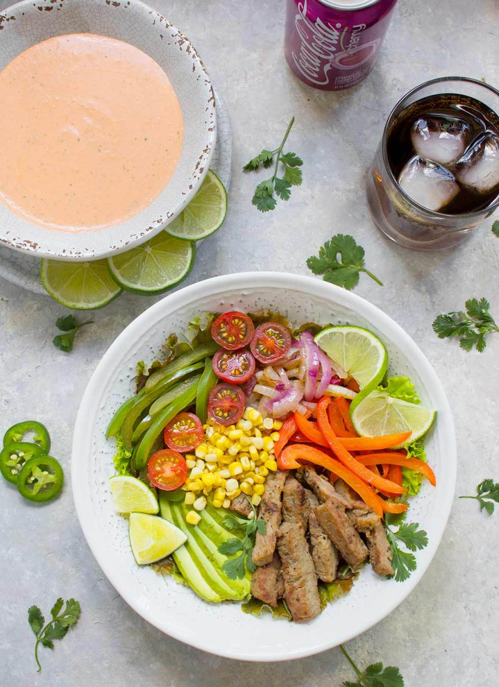 Beef Fajita Salad with Creamy Salsa Dressing, served in a bowl, with a glass of Cherry Coke. Recipe at SoupAddict.com