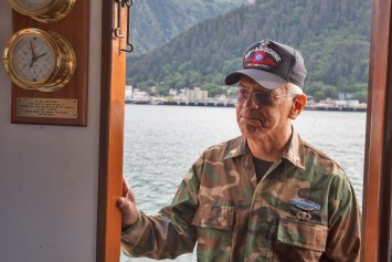 Dennis Jack, Tlingit from Angoon, stands in the doorway of the Princeton Hall, a safety boat, on Wednesday, June 8, 2016, near Juneau, Alaska. The One People Canoe Society group began the trip to Juneau from Angoon on June 2. Jack is one of several Alaska Native veterans who flew a flag honoring their brethren during the trip which is the unofficial beginning of Celebration. (Photo by Rashah McChesney/KTOO)