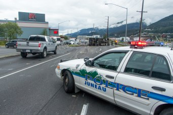 A Juneau Police Department cruiser closes the inbound lanes of Egan Drive after a truck rollover on July 25th, 2016. (Photo by Mikko Wilson / KTOO)