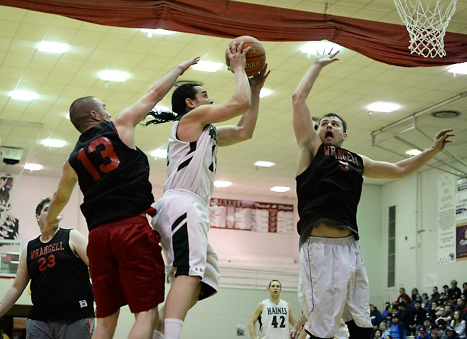 Wrangell's Mitch Mork (13) and Tony Harding (9) challenge a shot by Haines' Ryan Harms during their B-Bracket quarterfinal in the Juneau-Lions Club 71st Annual Gold Medal Basketball Tournament at Juneau-Douglas High School on Monday. Haines won 82-52. (Photo courtesy Klas Stolpe)
