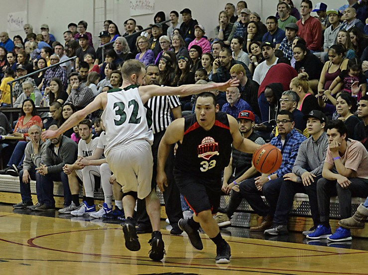 Hoonah's Jaylin Prince (33) dribbles past Haines' Tyler Healy (32) during the B-Bracket championship of the Juneau Lions Club 71st Annual Gold Medal Basketball Tournament at Juneau-Douglas High School on Saturday. Haines won 79-73. (Photo courtesy Klas Stolpe)