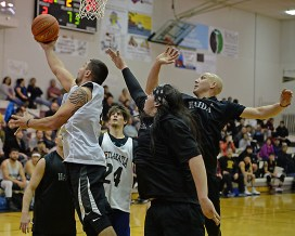 Metlakatla's Brian Hayward (2) scores against Hydaburg's Sebastian Bowker and Devin Edenshaw during their B-Bracket elimination game at the Juneau Lions Club 71st Annual Gold Medal Basketball Tournament at Juneau-Douglas High School on Tuesday. Hydaburg won 96-88. (Photo courtesy Klas Stolpe)