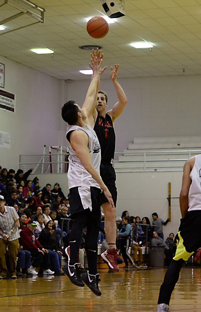 Wrangell's Ryan Howell shoots over Angoon's Bailey Johnson during their B-Bracket elimination game in the Juneau Lions Club 71st Annual Gold Medal Basketball Tournament at Juneau-Douglas High School on Thursday. Wrangell won 92-81. (Photo courtesy Klas Stolpe)