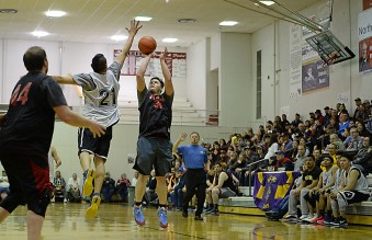 Wrangell's Eric James (34) scores over Angoon's Dustin Endicott (21) during their B-Bracket elimination game in the Juneau Lions Club 71st Annual Gold Medal Basketball Tournament at Juneau-Douglas High School on Thursday. Wrangell won 92-81. (Photo courtesy Klas Stolpe)