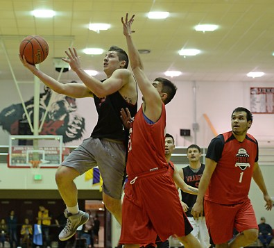 Wrangell's Andrew Versteeg scores against Hoonah's Charles Carteeti (10) during their B-Bracket elimination game in the Juneau Lions Club 71st Annual Gold Medal Basketball Tournament at Juneau-Douglas High School on Friday. Hoonah won 85-77. (Photo courtesy Klas Stolpe)