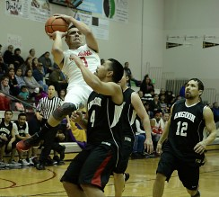 Hoonah's Anthony Lindoff (0) shoots over Angoon's Levi Johnson Sr. (4) during their C-Bracket elimination game at the Juneau Lions Club 71st Annual Gold Medal Basketball Tournament at Juneau-Douglas High School on Tuesday. Hoonah won 88-66. (Photo courtesy Klas Stolpe)