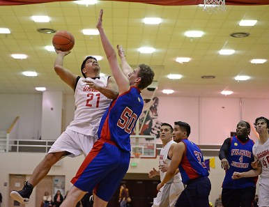 Hoonah's Lucas Johnson (21) shoots over Filcom's Steve Wall (50) during their C-Bracket elimination game in the Juneau Lions Club 71st Annual Gold Medal Basketball Tournament at Juneau-Douglas High School on Wednesday. Hoonah won 66-62. (Photo courtesy Klas Stolpe)